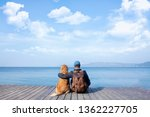 Dog And Man Sitting On Pier
