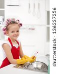Little girl with big curls doing the dishes - smiling, wearing large gloves - stock photo