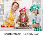 Kids helping mother preparing a salad in the kitchen - washing the vegetables - stock photo