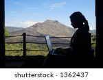 Silhouette of business woman working with a mountain in the background - stock photo