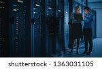 Stock photo in the modern data center engineer and it specialist work with server racks talking doing system 1363031105