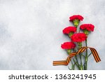 Red carnations and St. George ribbon on a concrete background. Symbol may 9, victory day. Copy space