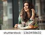 Stock photo portrait of attractive lady drinking coffee and eating breakfast at cafeteria 1363458632