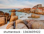 The giant granite rock boulders covered in orange and red lichen at the Bay of Fires in Tasmania, Australia look like the rocks are on fire - stock photo