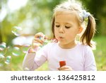 cute little girl is blowing a... | Shutterstock . vector #136425812