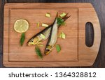 Stock photo two baltic herrings cold smoked with dill green onions and lime on a wooden cutting board two 1364328812