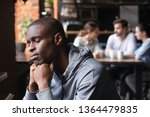 Stock photo frustrated sad african american guy sitting alone in cafeteria feels lonely people avoid 1364479835
