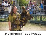 Small photo of BIOT - MARCH 31: Man holding a trained eagle in the Les Templiers party in Biot, on March 31, 2012 in France. The traditional event happens every year and the whole town becomes a medieval times city.
