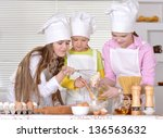 three cheerful girls baking a...   Shutterstock . vector #136563632