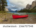 Empty red canoe on a rocky shoreline of a pristine alpine lake surrounded by mountains