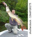 Fisherman Holding A Big Pike....