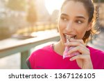 Stock photo athletic woman eating a protein bar closeup face of young sporty woman resting while biting a 1367126105