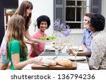 Serving appetisers to multi racial friends at a casual lunch gathering - stock photo