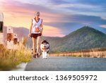 Stock photo woman doing daily exercise jogging on the public park road with puppy breed dog 1369505972