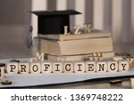 Small photo of Word PROFICIENCY composed of wooden dices. Black graduate hat and books in the background. Closeup
