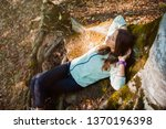 young woman resting at the base ... | Shutterstock . vector #1370196398