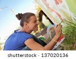 Woman Decorates The Walls Of...