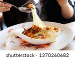 Small photo of Mashed potatoes baked with cheese Asian woman is giving a spoon To scoop the cheese from a small cup until the cheese is stretched into a long line due to the viscosity of the cheese