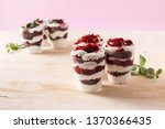 Small photo of Cake dessert. Trifle red velvet in plastic cup with strawberry jam and delicate cream and Trifle with chocolate biscuit, delicate cream, cherry and mint leaves.