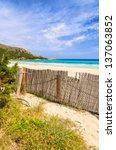 Small photo of Fence flowers sand dune beach turquoise sea water, Cala Agulla, Majorca island, Spain