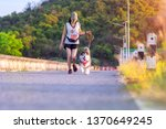Stock photo woman doing daily exercise jogging on the public park road with puppy breed dog 1370649245