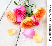 Bouquet of beautiful orange and pink roses on rustic wood table. - stock photo