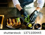 A Chef Plating Tacos In A...