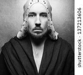 Art-fashion ethnic portrait of a serious king-warrior in white cape with silver metal pricks posing over gray background. Retro (vintage) style. Black and white (monochrome) studio shot. - stock photo