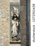 Small photo of Sculpture of of Archangel Michael, monumental standing figure on the outer side of the flying buttress pier at medieval Gothic Black Church in Brasov city. Transylvania, Romania