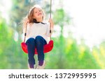 little smiling girl swinging on ... | Shutterstock . vector #1372995995
