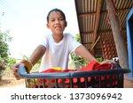 asian boy bring clothes basket... | Shutterstock . vector #1373096942