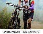 dirty cyclist climbing uphill... | Shutterstock . vector #1374296078