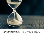 Small photo of Sand running through the bulbs of an hourglass measuring the passing time in a countdown to a deadline, on a dark background with copy space.
