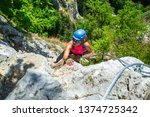 "Small photo of Adventurous, courageous woman climber on a via ferrata route called ""Casa Zmeului"", a popular tourist attraction near Vadu Crisului, Romania. Active tourism in Padurea Craiului mountains, Apuseni."