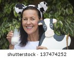 Small photo of Portrait attractive mature woman happy relaxed friendly with glass of milk in hand downy beard or milksop, funny cow ears on head and wooden cow in arm outdoor with blurred background.