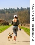Stock photo girl running with dog outdoors in nature on a road to forest sunny day countryside sunset 1375047992