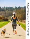 Stock photo girl running with dog outdoors in nature on a road to forest sunny day countryside sunset 1375047995