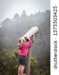 a young girl looks through... | Shutterstock . vector #1375503425