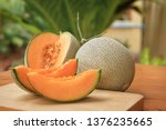 Whole and sliced of Japanese melons,honey melon or cantaloupe (Cucumis melo) on wooden table background.Favorite fruit in summer.Food,Fruits or healthcare concept.