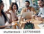 Small photo of Mutual understanding. Group of young modern people in smart casual wear discussing something and smiling while working in the creative office