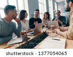 Small photo of Confident and smart. Group of young modern people in smart casual wear discussing something and smiling while working in the creative office