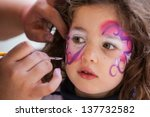 A Girl Has Her Face Painted In...