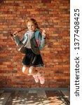 cute schoolgirl with schoolbag... | Shutterstock . vector #1377408425