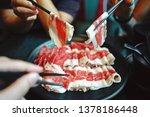 Small photo of Hands of diversity people using chopsticks to pick up raw sliced beef for eating Shabu Shabu or Sukiyaki dipping and dropping. Food is cooked piece by piece by the diner at table. (selective focus)