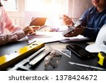 Stock photo engineers pointing to building on blueprint and using laptop to drawing design building project in 1378424672
