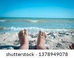 small feet in sand on a beach.... | Shutterstock . vector #1378949078