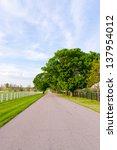 Country road surrounded the horse farms at spring. - stock photo