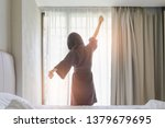 Stock photo woman stretching in bed after waking up back view woman sitting near the big white window while 1379679695
