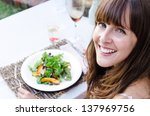 Beautiful woman having salad at restaurant alfresco dining, copy space - stock photo