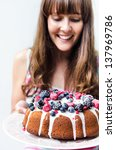 Happy woman serving a mixed berry bundt cake with glaze icing, freshly baked seasonal sweet dessert - stock photo